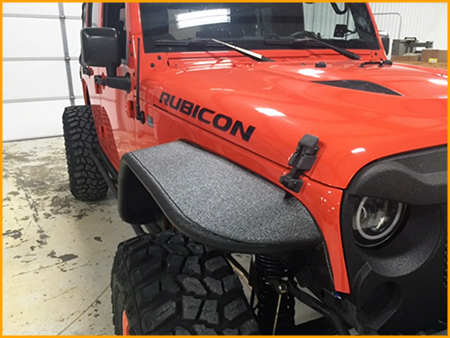 Front fenders, grill, front and rear bumper of Jeep Rubicon sprayed with GatorHyde polyurea